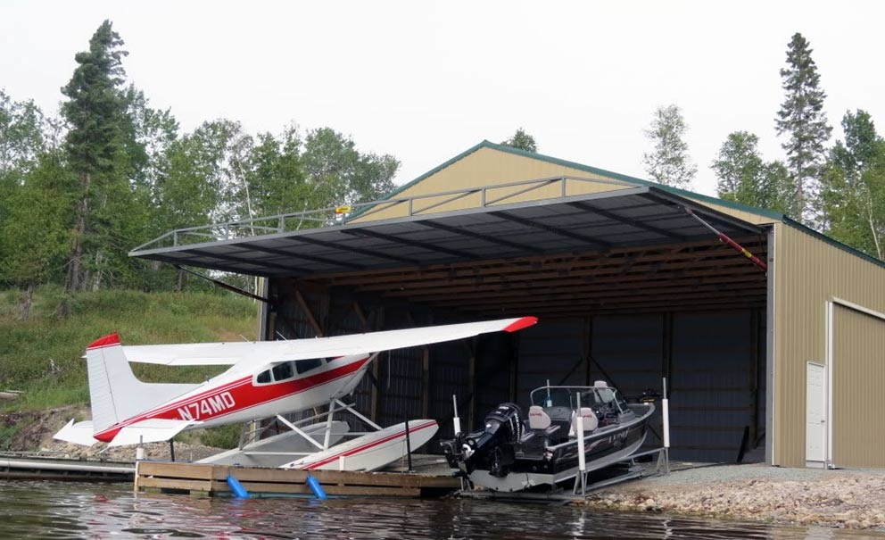 A sea plane being loaded into a waterside hangar